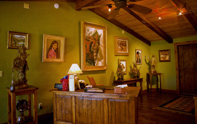 Coleman's studio is filled with his own artwork and that of his peers, including a painting by the late Ray Swanson (center) flanked by a portrait by Don Crowley.