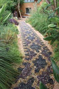 Anne's pebble mosaic footpath winds organically through a lush garden.