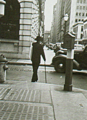 Maynard Dixon on San Francisco Street, circa 1930, carrying a painting and clutching his swordcane.