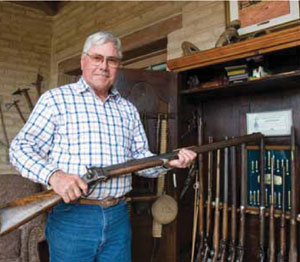 Fred handles one of the many classic rifles, pistols and buffalo guns he has collected over the years. Many of the guns have colorful history, including one specimen used at the Battle of the Little Big Horn. Early in his career, Fred used to exchange paintings for guns, which he later traded for cash. Then he started to repair and eventually build his own collection.